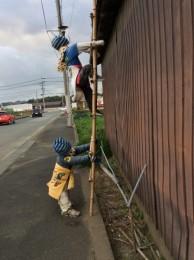 子どもが梯子を登っている案山子。